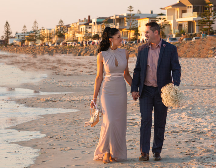 The newly married couple walking hand in hand along the beach after their wedding ceremony.