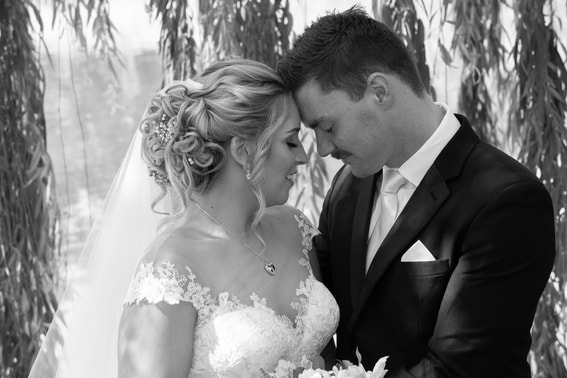 Black and white of the Bride and groom touching foreheads with their eyes closed.