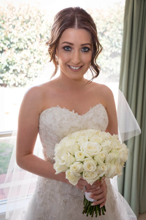 Our bride at home before the ceremony holding her wedding bouquet